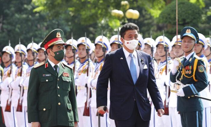 Министр обороны Вьетнама Фан Ван Занг (слева) и министр обороны Японии Нобуо Киси проходят почётный караул в Ханое, Вьетнам, 12 сентября 2021 г