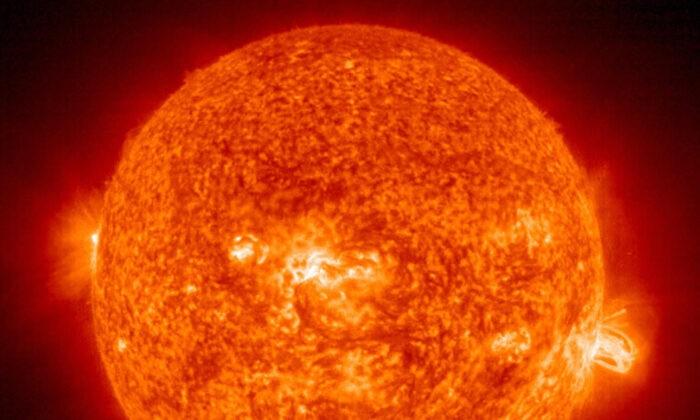Солнечная вспышка (справа), извергающаяся из гигантского солнечного пятна 649. Мощный взрыв привёл к корональному выбросу в космос. Он был направлен к Земле 19 августа 2004 г. HO/AFP via Getty Images | Epoch Times Россия