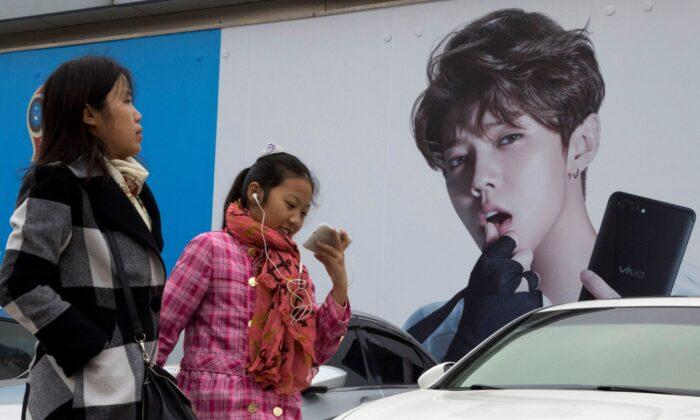 Китайские женщины проходят мимо рекламы кумира подростков Лу Хана, также известного как китайский Джастин Бибер, в Пекине, Китай, 21 октября 2017 г. (Ng Han Guan / AP Photo) | Epoch Times Россия