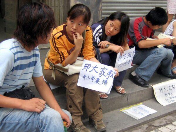 Студенты и выпускники вузов, сидя на тротуаре, предлагают свои услуги в китайской провинции Шань. Миллионы молодых специалистов с университетским образованием остаются без работы. (STR/AFP/Getty Images)