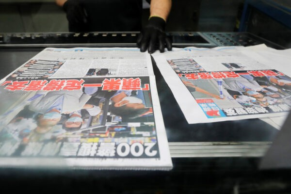 Сотрудник проверяет качество печати экземпляров газеты Apple Daily, издаваемой Next Media Ltd, с заголовком «Apple Daily продолжит борьбу» после того, как медиа-магнат Джимми Лай Чи-ин, основатель Apple Daily, был арестован в типографии компании в Гонконге, Китай, 11 августа 2020 г. Tyrone Siu / Reuters
