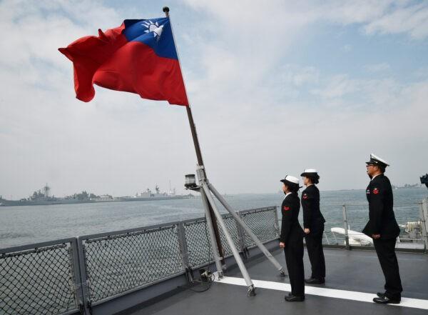 Тайваньские моряки приветствуют флаг острова на палубе корабля Panshih после участия в ежегодных учениях на военно-морской базе Tsoying в Гаосюне, Тайвань, 31 января 2018 г. Mandy Cheng / AFP via Getty Images