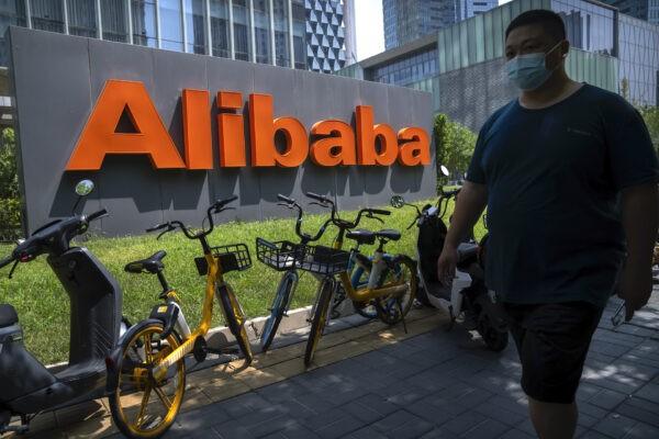 Мужчина в маске проходит мимо офиса китайской компании электронной коммерции Alibaba в Пекине, 10 августа 2021 г. AP Photo / Mark Schiefelbein