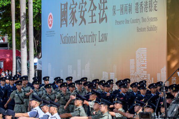 Участники военного парада маршируют рядом с плакатом в поддержку нового закона о национальной безопасности в конце церемонии поднятия флага по случаю 23-й годовщины передачи Гонконга от Великобритании Китая. Гонконг, 1 июля 2020 г. Anthony Wallace / AFP via Getty Images