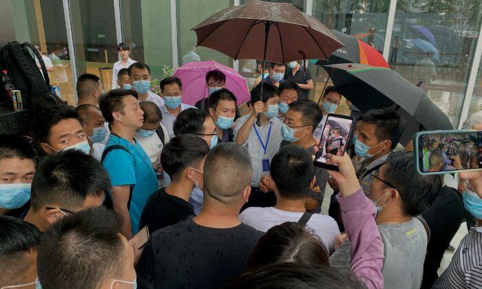 Люди собираются возле штаб-квартиры Evergrande в Шэньчжэне, на юго-востоке Китая, 14 сентября 2021 г.