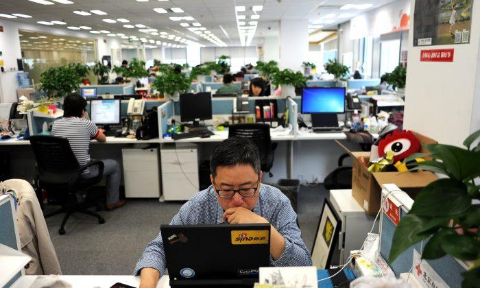 Мужчина за ноутбуком в офисе Sina Weibo, широко известной как китайская версия Twitter, в Пекине, 16 апреля 2014 г. Wang Zhao/AFP/Getty Images | Epoch Times Россия