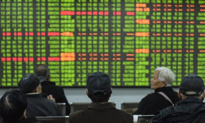 Инвесторы смотрят на экран, показывающий движение фондового рынка компании по ценным бумагам в городе Ханчжоу в восточной провинции Китая Чжэцзян, 3 февраля 2020 г. STR/AFP via Getty Images | Epoch Times Россия