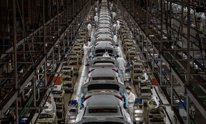 Сотрудники работают на сборочной линии автомобильного завода Dongfeng Honda в Ухане, центральная китайская провинция Хубэй, 23 марта 2020 г. STR / AFP | Epoch Times Россия