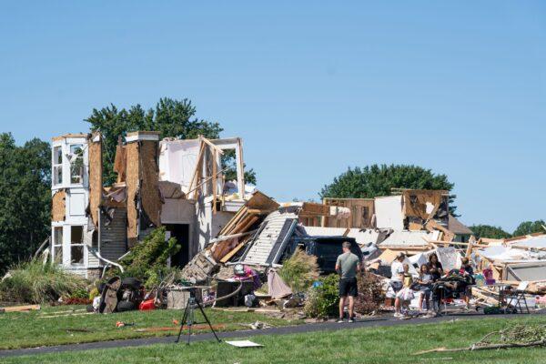 Люди стоят у дома, повреждённого торнадо в Муллика-Хилл, штат Нью-Джерси, 2 сентября 2021 г. Branden Eastwood/AFP via Getty Images