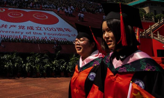 Два выпускника проходят мимо большого плаката к столетию компартии Китая в Уханьском университете в Ухане, Китай, 23 июня 2021 г. Getty Images | Epoch Times Россия