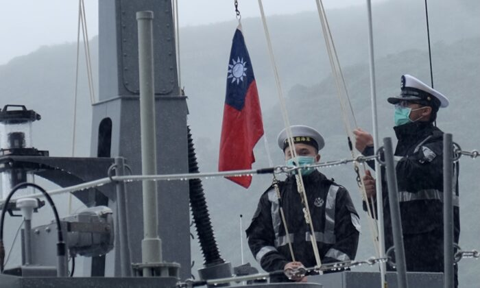 Двое военнослужащих ВМС Тайваня поднимают государственный флаг во время официальной церемонии на верфи в Суао, городке в восточном тайваньском уезде Илань, 15 декабря 2020 г. Sam Yeh / AFP via Getty Images | Epoch Times Россия