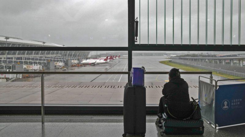 Пассажирка сидит насвоём багаже после отмены всех рейсов вмеждународном аэропорту Пудун вШанхае, Китай, 25июля 2021 года. (Andy Wong/AP Photo)  | Epoch Times Россия