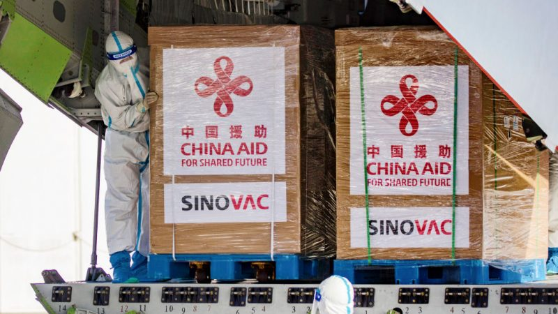 Персонал в защитных костюмах обрабатывает ящики, содержащие вакцины Sinovac Biotech COVID-19, на борту самолета ВВС Китая. Фото: Эзры Акааяна / Getty Images | Epoch Times Россия