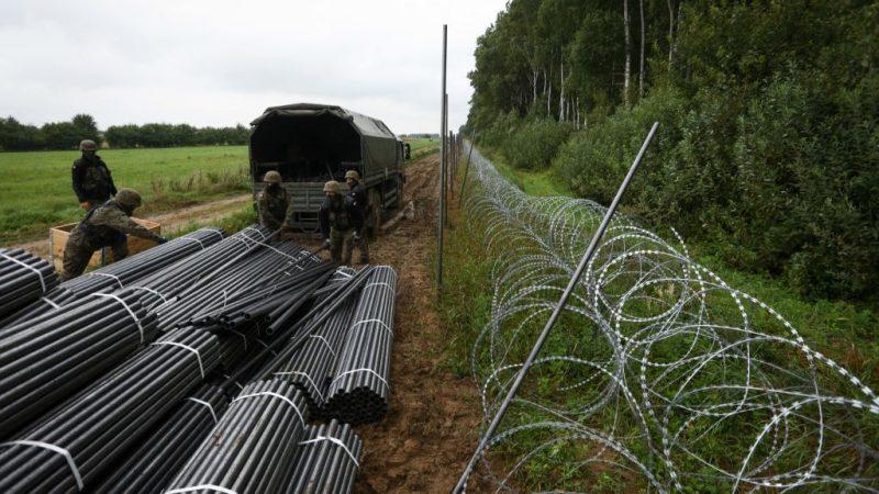 Польские солдаты разгружают материалы для строительства забора из колючей проволоки на границе с Беларусью в Зубжице-Вельке недалеко от Белостока, восточная Польша, 26 августа 2021 года. (JAAP ARRIENS/AFP via Getty Images)  | Epoch Times Россия