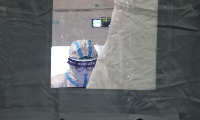 Лаборант в средствах индивидуальной защиты в Сямыне, в восточной провинции Фуцзянь, Китай, 16 сентября 2021 г. (STR / AFP через Getty Images) | Epoch Times Россия