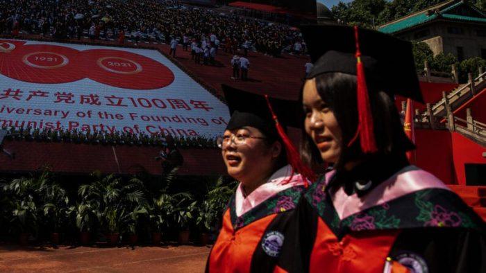 Две выпускницы университета проходят возле большого экрана, посвящённого 100-летию  компартии в Уханьском университете, Ухань, Китай, 23 июня 2001 г. (Getty Images)   | Epoch Times Россия