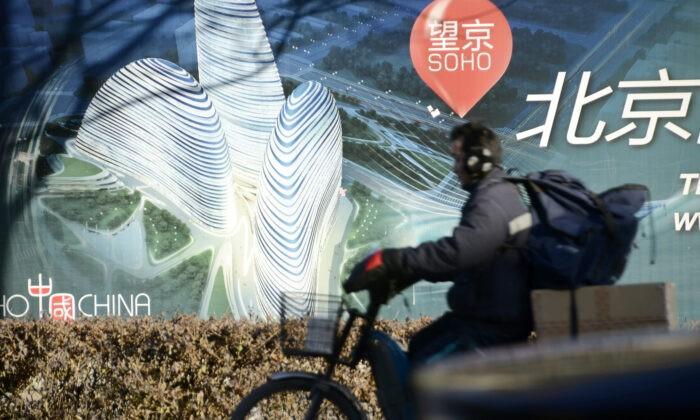 Велосипедист  у рекламного щита строящегося комплекса Wangjing  SOHO известного архитектора Zaha Hadid в Пекине 3 января, 2013.года, (Wang Zhao/AFP via Getty Images) | Epoch Times Россия