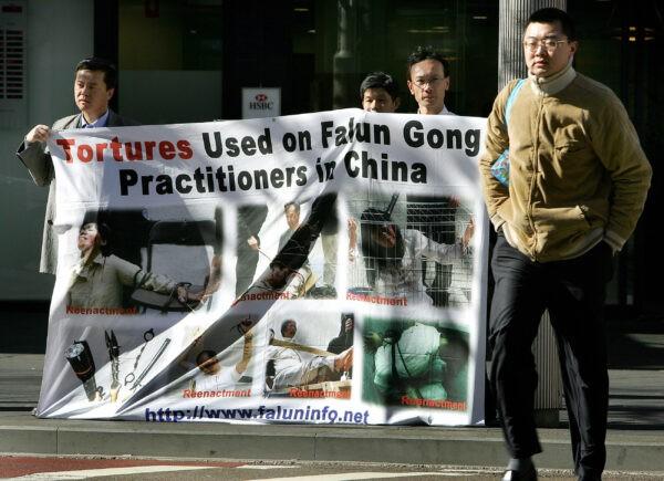 Последователи Фалуньгун вывесили плакат у китайского квартала в Сиднее, 20 июля 2005 г. (Greg Wood/AFP via Getty Images)
