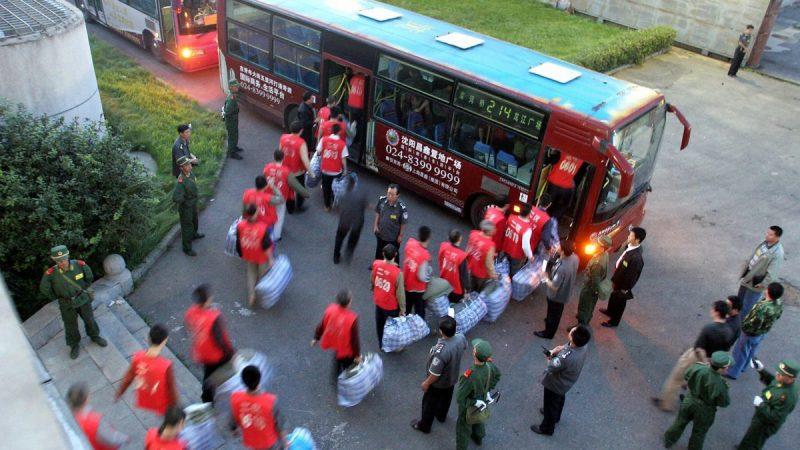 Китайские заключённые садятся в автобус под охраной, направляясь в недавно построенную тюрьму в Шэньяне, северо-восточная китайская провинция Ляонин, 20 августа 2005. (AFP/AFP/Getty Images) | Epoch Times Россия