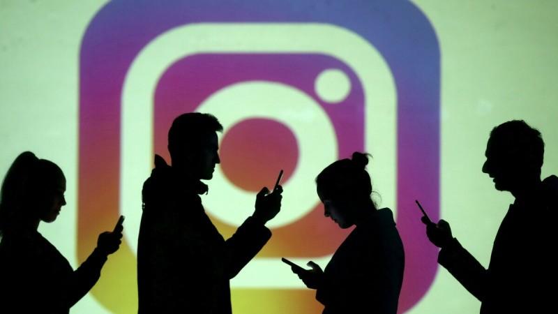 Силуэты мобильных пользователей видны рядом с проекцией на экран логотипа Instagram на этой иллюстрации, сделанной 28 марта 2018 г. (Dado Ruvic / Illustration / Reuters)    Epoch Times Россия