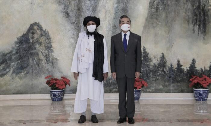 Сооснователь Талибана мулла Абдул Гани Барадар (слева) и министр иностранных дел Китая Ван И позируют фотографу во время встречи в Тяньцзине, Китай, 28 июля 2021 г. (Li Ran/Xinhua via AP)    Epoch Times Россия