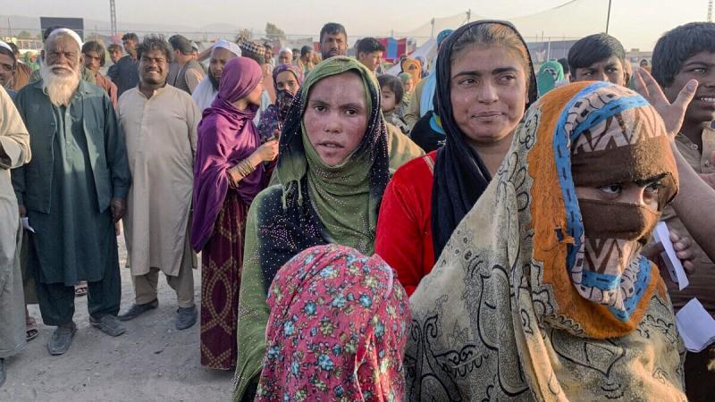 Афганские семьи получают продукты, которые раздаёт христианская организация из Исламабада, на окраине Чамана, города на юго-западе пакистанской провинции Белуджистан, на границе с Афганистаном, 31 августа 2021 года. Десятки афганских семей пересекли границу Пакистана, спасаясь от талибов. (AP Photo)  | Epoch Times Россия