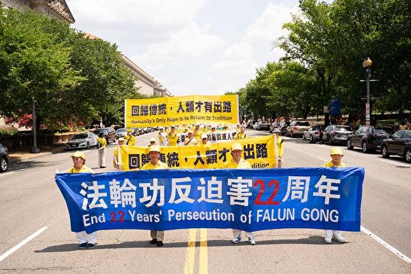 Последователи Фалуньгун несут баннер с призывом остановить 22-летнее преследование Фалуньгун во время парада в Вашингтоне, округ Колумбия, 16 июля 2021 года.