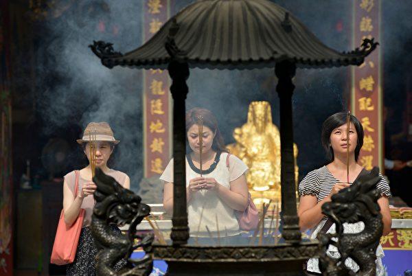 Женщины молятся перед храмом городского бога Тайбэя Ся-Хай, Тайбэй, Тайвань, 21 мая 2018 года. (Chris Stowers/AFP)
