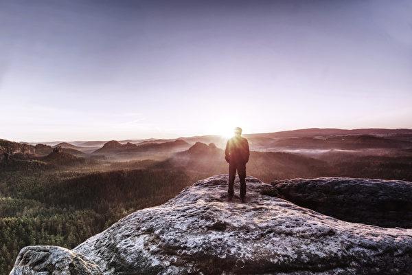 Человек стоит на скалистой вершине на фоне восходящего солнца. (shutterstock)    Epoch Times Россия