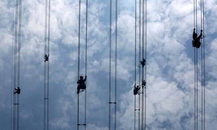 Рабочие сетевого оператора China Southern Power Grid проверяют силовые кабели, соединяющие опоры электропередач в Дунгуане, провинция Гуандун, Китай, 29 мая 2018 года. (Stringer / Reuters) | Epoch Times Россия