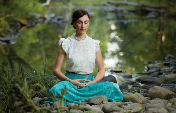 Автор и исполнитель песен Кэти Мантык медитирует по практике Фалунь Дафа у реки, она сидит со сложенными ногами и сцепленными руками. (Изображение: Binggan Zhang)  | Epoch Times Россия