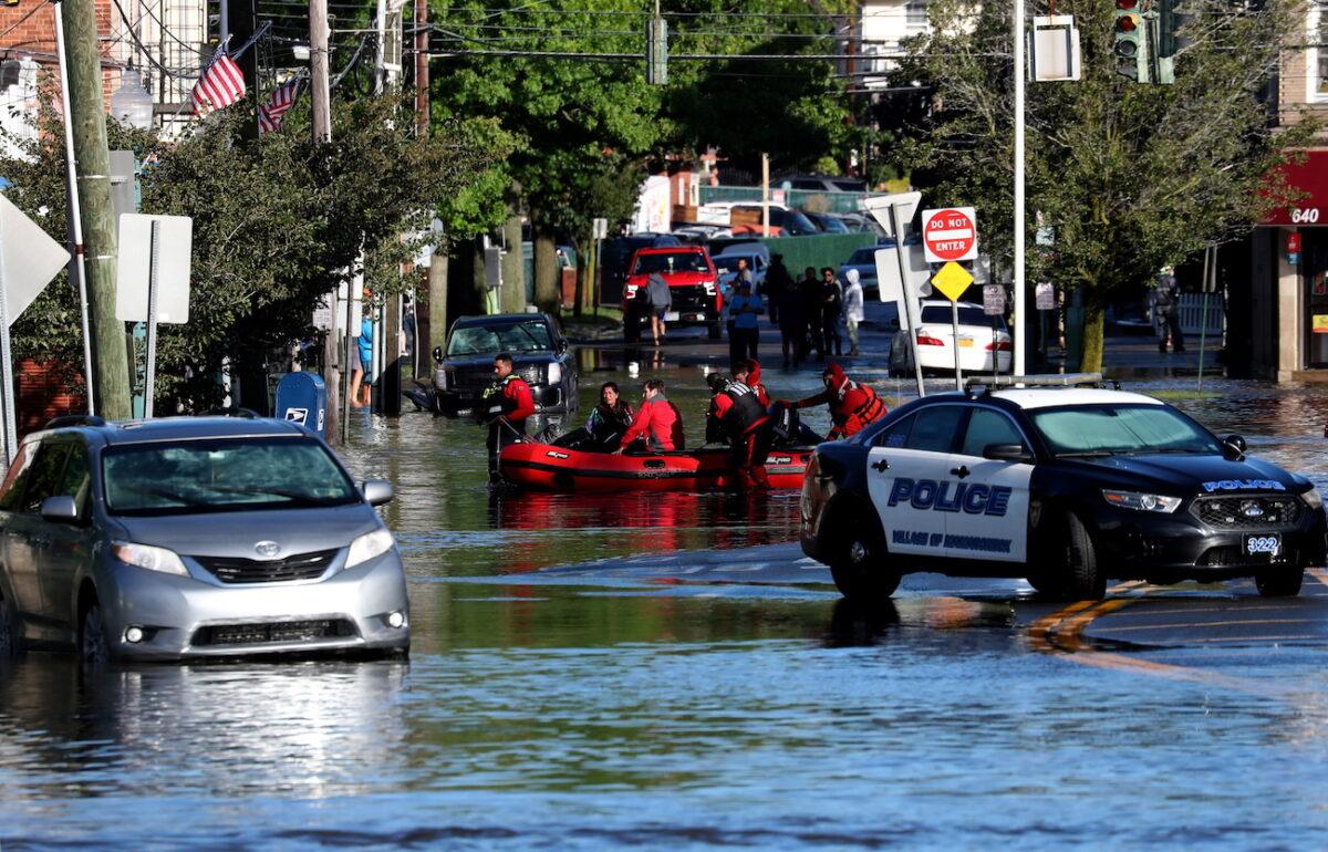 Службы быстрого реагирования тянут местных жителей на лодке, оказавшихся в ловушке паводковых вод, в Мамаронеке, штат Нью-Йорк, 2 сентября 2021 г. (Mike Segar/Reuters)