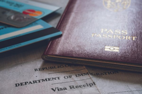 Фотография паспорта и кредитных карт, лежащих поверх проездного документа. Некоторые состоятельные люди остаются работать в Китае, но имеют несколько паспортов и готовы в любой момент сбежать. (Изображение: Jon Anders Wilken via Dreamstime)