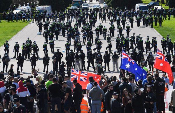 Полиция арестовывает строительных рабочих и демонстрантов на ступенях Храма памяти во время акции протеста против правил COVID-19 в Мельбурне, Австралия, 22 сентября 2021 г. William West / AFP via Getty Images
