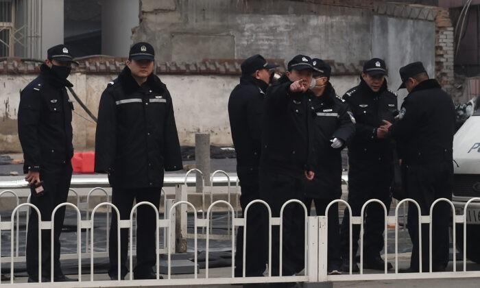 Полицейские стоят на страже у Народного суда промежуточной инстанции № 2, где 22 декабря 2015 года в Пекине был вынесен приговор адвокату по правам человека Пу Чжицяну. Greg Baker/AFP via Getty Images | Epoch Times Россия