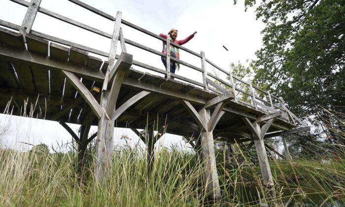 Силке Ломанн из Summers Place Auctions стоит на оригинальном мосту Пухстикс из Эшдаун Форест, изображённом в книгах А. А. Милна о Винни Пухе и иллюстрациях Э. Х. Шепарда, недалеко от его первоначального местоположения в Тонбридже, Кент, Англия, 30 сентября 2021 г. Gareth Fuller/PA via AP | Epoch Times Россия