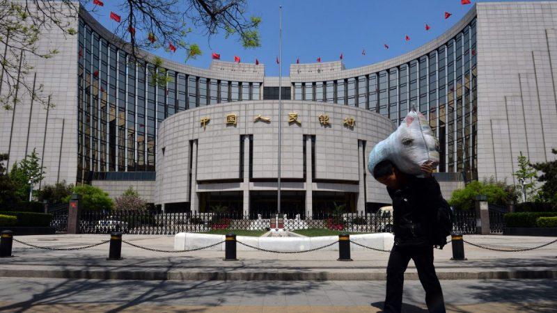 Китайский рабочий-мигрант проходит мимо Народного банка Китая, направляясь на автобусную станцию в Пекине, 1 мая 2013 года. (Mark Ralston/AFP/Getty Images)  | Epoch Times Россия