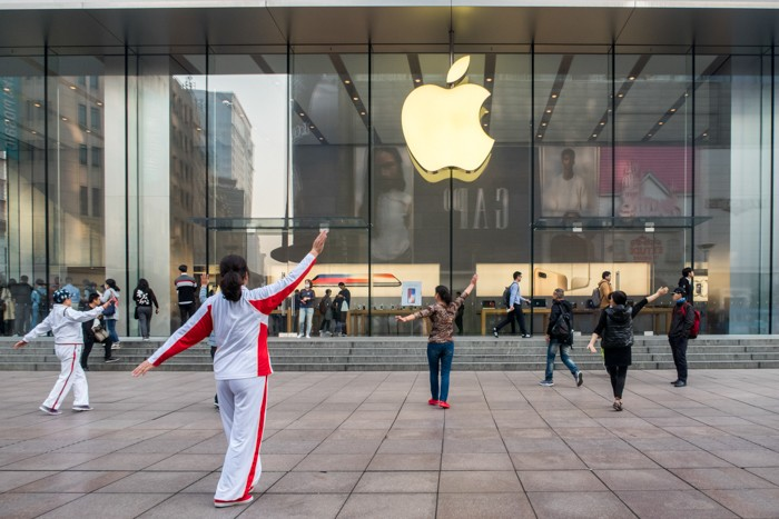 SHANGHAI, CHINA - NOVEMBER 03: Elderly people perform square dance in front of an Apple store on Nanjing East Road on November 3, 2017 in Shanghai, China. iPhone X go on sale on Friday and people who pre-ordered online will also start receiving their devices. (Photo by VCG/VCG via Getty Images)