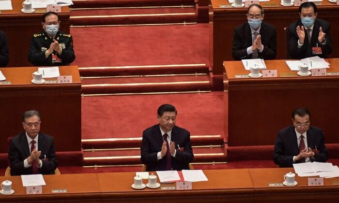 Член Постоянного комитета Политбюро Ван Ян (слева), лидер Китая Си Цзиньпин (в центре) и премьер Ли Кэцян аплодируют после объявления результатов голосования по изменениям в избирательной системе Гонконга на заключительном заседании Всекитайского собрания народных представителей, в Большом зале народных собраний в Пекине, 11 марта 2021 г. Nicolas Asfouri/AFP via Getty Images | Epoch Times Россия