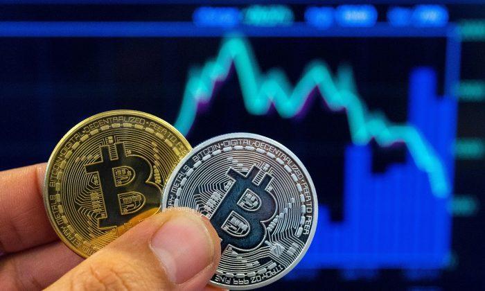 Человек держит изображение криптовалюты биткойн в магазине Bitcoin Change в израильском городе Тель-Авиве 6 февраля 2018 г. Jack Guez/AFP/Getty Images | Epoch Times Россия