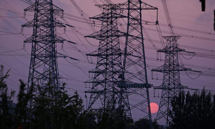 Солнце садится за опоры линий электропередач в Пекине 28 сентября 2021 г. Leo Ramirez/AFP via Getty Images | Epoch Times Россия
