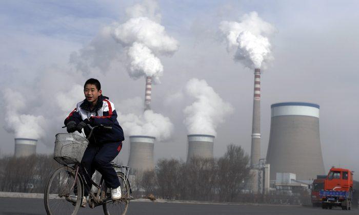 Китайский мальчик проезжает мимо градирен угольной электростанции в Дадуне, провинция Шаньси, Китай, 3 декабря 2009 г. Andy Wong / AP | Epoch Times Россия