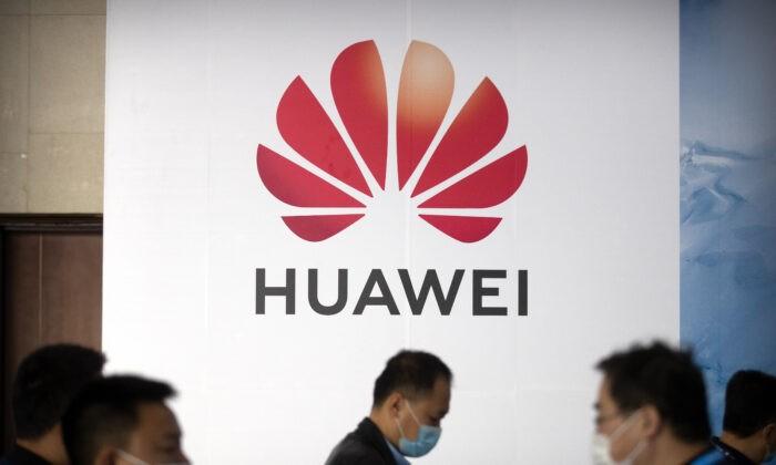 Люди проходят мимо рекламного щита китайской технологической компании Huawei на выставке PT Expo в Пекине 14 октября 2020 г. AP Photo / Mark Schiefelbein | Epoch Times Россия