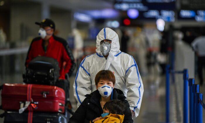 Пассажиры в масках прибывают в международный аэропорт Пудун в Шанхае 19 марта 2020 г. Hector Retamal/AFP via Getty Images   Epoch Times Россия