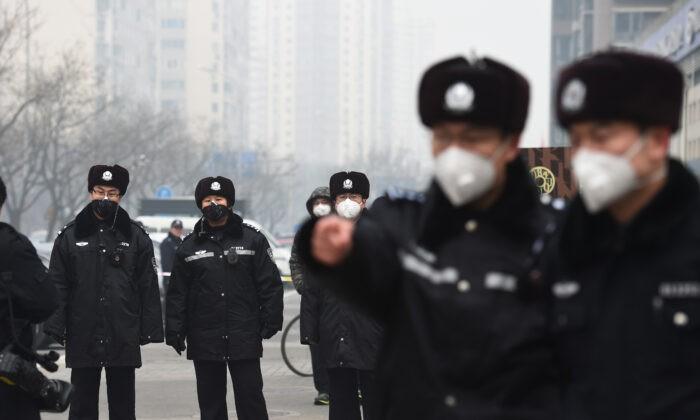Полиция в масках стоит на страже у Народного суда промежуточной инстанции № 2, где 22 декабря 2015 г. в Пекине был вынесен приговор адвокату по правам человека Пу Чжицяну. Greg Baker/AFP via Getty Images | Epoch Times Россия