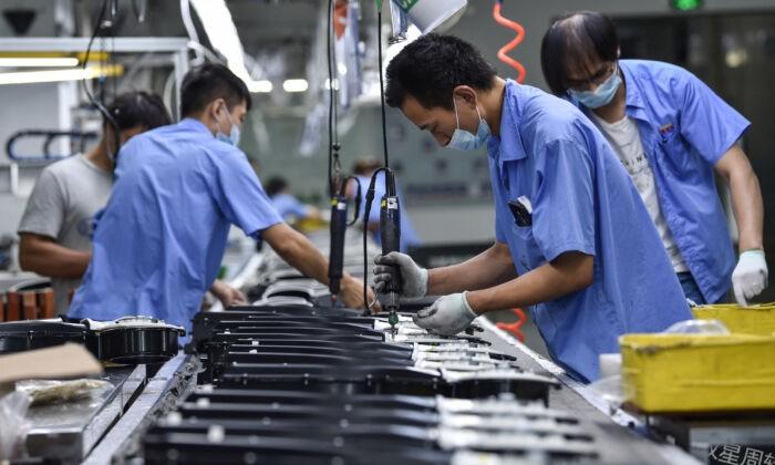 Рабочие производят детали стиральных машин на заводе в Нанкине, в восточной провинции Китая Цзянсу, 16 августа 2021 г. STR / AFP   Epoch Times Россия