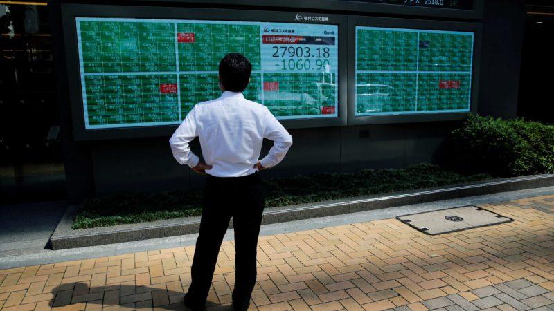 Мужчина смотрит на электрическое табло с индексом Nikkei у брокерской компании в деловом районе Токио, Япония, 21 июня 2021 г. (Kim Kyung-Hoon / Reuters)   Epoch Times Россия