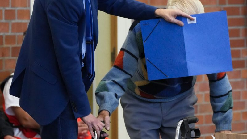 Адвокат Стефан Ватеркамп закрывает лицо обвиняемого Йозефа С., когда они прибывают в зал суда в Бранденбурге, Германия, 7 октября 2021 г. (Markus Schreiber / AP Photo)   Epoch Times Россия