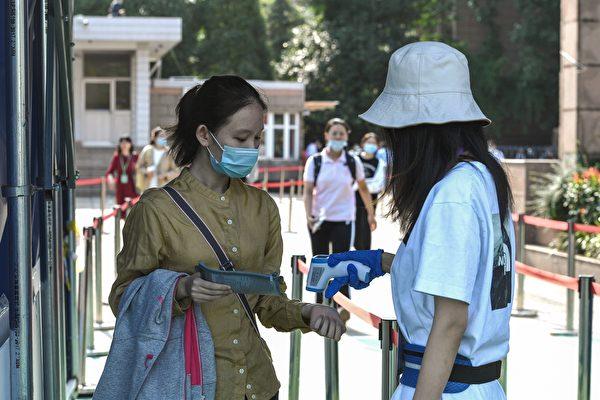Устудентки (слева) проверяют температуру тела перед входом вшколу для сдачи национального вступительного экзамена (NCEE), известного как гаокао, вНанкине, ввосточной китайской провинции Цзянсу, 7июля 2020 года. (STR/AFP via Getty Images)