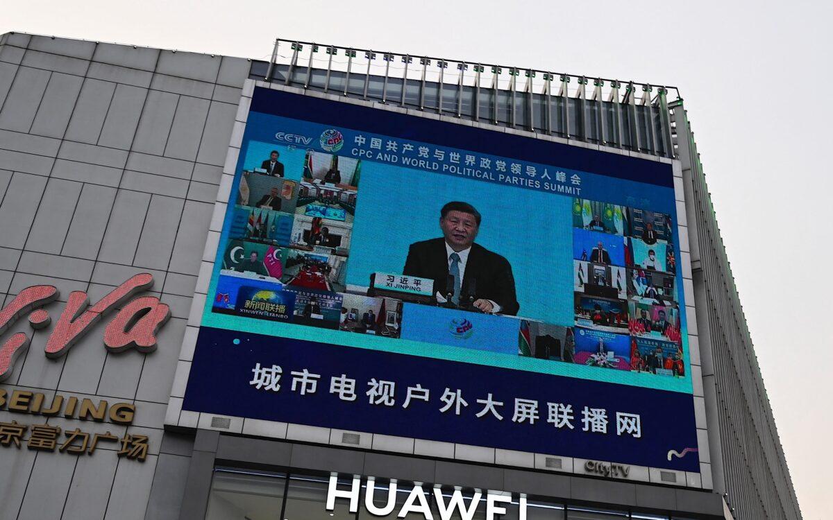 Трансляция на экране репортажа о выступлении китайского лидера Си Цзиньпина во время саммита компартии Китая и мировых политических партий, снаружи торгового центра в Пекине 7 июля 2021 года. (Jade Gai/AFP via Getty Images)